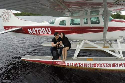 Man and woman sitting on the outside of an airplane on the water